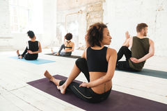 Group of multicultural young people practicing yoga. In a studio royalty free stock image