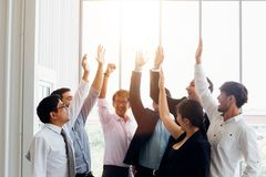 Cheerful diverse business people holding arms raised stock photo