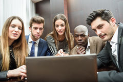 Group of multiethnic busy people looking at a laptop Royalty Free Stock Images