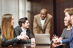 Group of multiethnic busy people working in an office. Black men explaining his project to the working group. Businesspeople, teamwork. Group of multiethnic busy Stock Photography