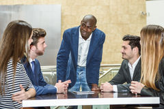 Group of multiethnic busy people working in an office. Businesspeople, teamwork. Group of multiethnic busy people working in an office with a black businessman Royalty Free Stock Photography