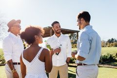 Group of multiethnic friends drinking and socialising. Young people having party at outdoor restaurant on a summer day Royalty Free Stock Photography