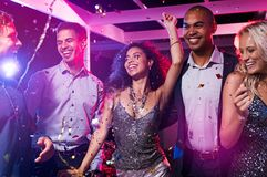 Friends dance at disco club. Group of multiethnic happy friends dancing at disco club. Group of young men and beautiful women having fun at celebration with Stock Images