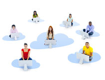 Group of Multiethnic People Sitting on a Cloud with Computer Stock Images
