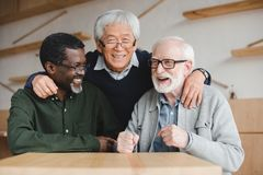 Senior friends embracing in bar. Group of multiethnic senior friends embracing in bar Royalty Free Stock Photo