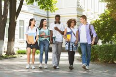 Group of multiethnic students walking together outdoors in college campus