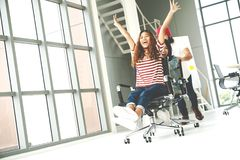 Group of multiethnic young creative teamwork having fun laughing and smiling in office chairs pushing. Coworker celebrating for su. Ccess feeling happy, enjoy royalty free stock photo