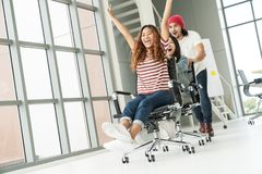 Group of multiethnic young creative teamwork having fun laughing and smiling in office chairs pushing. Coworker celebrating for su. Ccess feeling happy, enjoy stock photo