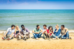 Group of multiracial best friends talking at beach. Group of international best friends sitting at beach talking with each other - Concept of multi cultural Stock Images