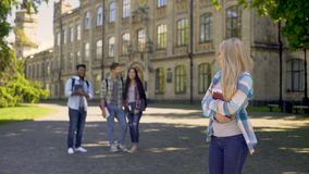 Group of multiracial fellows mocking humble newcomer girl at university. Stock footage stock video footage