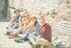 Group of multiracial friends taking a selfie with a mobile smartphone camera - Self portrait of happy persons. Sitting on the street and listening music with a stock photography