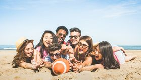 Group of multiracial happy friends having fun playing sport beach games - International concept of summer joy and multicultural f. Multiracial happy friends royalty free stock images