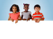 Group of multiracial kids portrait with white board. Royalty Free Stock Images