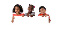 Group of multiracial kids portrait with white board.Isolated. Group of multiracial kids portrait in studio with white board.Isolated royalty free stock photos