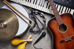 A group of musical instruments. Including a guitar, drum, keyboard, tambourine and microphone royalty free stock photo
