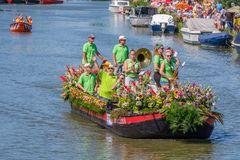 Group of musicians in green shirts on a beautiful boat decorated. SCHIPLUIDEN, THE NETHERLANDS - AUG 03, 2018 : Group of musicians in green shirts on a beautiful royalty free stock photos