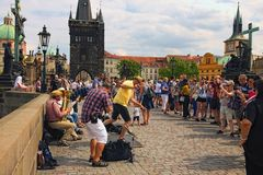 A group of musicians performs a song with a tap dance on the Charles Bridge in Prague. Cloudy summer day. Prague, Czech Republic-AUGUST 21,2018: A group of stock images