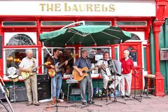 Performers busking on the streets of Killarney, Ireland. Group of musicians playing various instruments, busking on the streets of Killarney, Ireland stock image