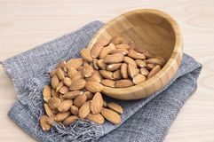 almonds falling from a bowl stock image
