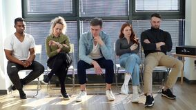 Group of nervous diverse ethnicity candidates waiting job interview in modern office lobby.