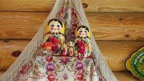 Group of nested dolls on a shelf in the background towels and wooden wall stock video