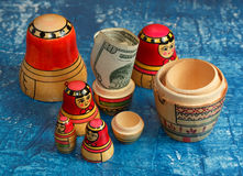 Group nesting dolls and dollars on a blue background Royalty Free Stock Photography