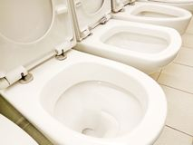 Group of new clean white opened toilet bowls stock images