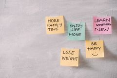 Group of New year Resolution Notes on pink, yellow, orange and green on wall written with  message of more family time, lose stock image