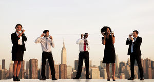 A Group Of New York Office Workers Communicating Via Cup Communicator. A group of office workers communicating via cup communicator royalty free stock photos
