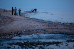 Group of night fishermen. JURKALNE, LATVIA - JULY 28, 2015: group of night fishermen preparing for fishing Stock Photo