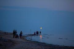 Group of night fishermen launching paper lantern Stock Image