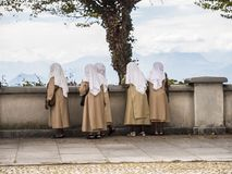 Group of nuns on terrace. Back view of religious nun community with heads covered standing on stone terrace exploring landscape Royalty Free Stock Images