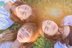 Group o beautiful girl are laying on the sunny glade with smail an. Beautiful asian girls are laying on the sunny glade with smail and close eyes.Dress in casual Royalty Free Stock Images
