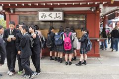 Group o schoolboys and girls buying omikuji paper fortune Sensoji Tokyo royalty free stock photography