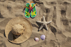 Group of objects on the sand. Hat, sandals, seashells and starfish on the sand. Beach items. Travel and vacation items Royalty Free Stock Photo