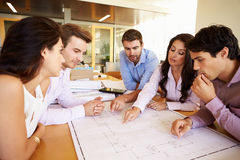 Group Of Architects Discussing Plans In Modern Office Stock Photography