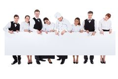 Group Of Catering Staff Holding A Blank Banner Stock Image