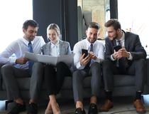 Free Group Of Four Business People Sitting On Sofa. They Couldn`t Be Happier About Working Together Stock Photos - 145559483