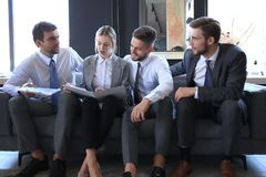 Free Group Of Four Business People Sitting On Sofa. They Couldn`t Be Happier About Working Together Stock Photo - 147401950