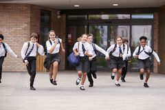 Free Group Of High School Students Wearing Uniform Running Out Of School Buildings Towards Camera At The End Of Class Stock Images - 134207834