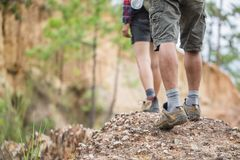 Group Of Man And Women Are Walking Trough Forest Path Wearing Mountain Boots And Walking Sticks. Low Section View Stock Photos
