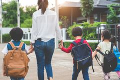 Free Group Of Mother And Kids Holding Hands Going To School With Schoolbag. Mom Bring Children Walk To School By Bus Together With Sat Stock Image - 132866201