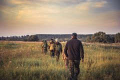 Free Group Of People In A Row Going Away Through Rural Field At Sunset During Hunting Season In Countryside Royalty Free Stock Photo - 100298185