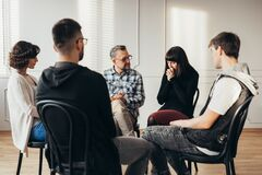 Free Group Of People Of Different Ages Sits In A Circle During A Meeting With A Professional Therapist Stock Photography - 179627252