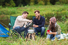 Group Of Smiling Tourists Cooking Food In Camping Royalty Free Stock Images