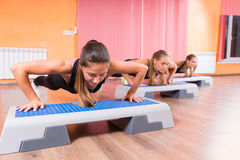 Group Of Women Strengthening Cores In Step Class Royalty Free Stock Images