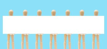 Group Of Wooden Figure Mannequin Holding Empty Space White Paper In Hand. Stock Photo