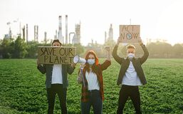 Free Group Of Young Activists With Placards Standing Outdoors By Oil Refinery, Protesting. Royalty Free Stock Photos - 184969758