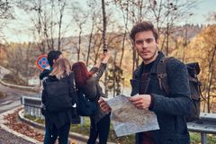 Free Group Of Young Hikers Standing On The Road Sidelines At Beautiful Autumn Forest, Guy With Map Planning Hike. Stock Photo - 130229380