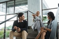 Group of office friends chatting sit on the stairs when break. In the office building stock photography